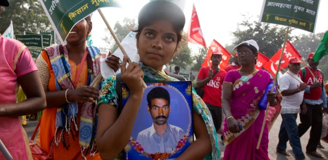 "A family member of an Indian farmers carries photograph of her relative who committed suicide as farmers arrive in the Indian capital for a two day's protest in New Delhi, India, Thursday, Nov.29, 2018. Failed harvests force poor farmers to borrow money at high interest rates to buy seeds, fertilizers and food for their cattle. They often mortgage their land and, as debts mount, some are driven to suicide. Placard on right reads, ""Debt free farmer- Suicide free India""."