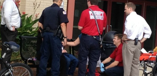 Prompt paramedics Wayne Van Beveren (standing with red shirt) and EMT Chris Spizak (red shirt, crouching) arrive on the scene to treat a high school student. Paramedics will soon use new technology such as Skype to better assess a patients condition with a doctor.