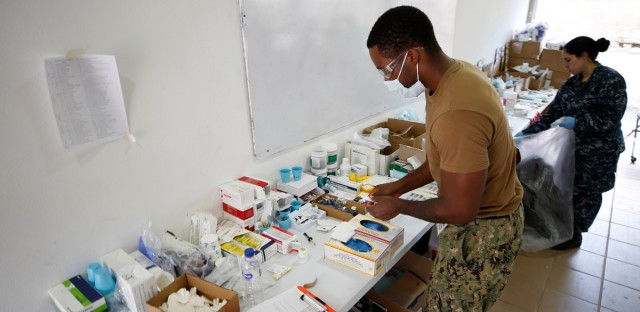 A U.S. military doctor organizes supplies and medicine after attending patients at a school in Riohacha, Colombia, Monday, Nov. 26, 2018. The USNS Comfort is in Colombia as part of a mission to treat local residents and Venezuelas who require urgent medical attention.