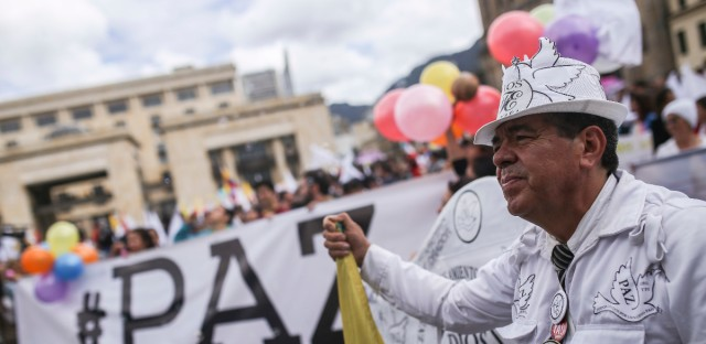 Supporters of the peace deal with rebels of the Revolutionary Armed Forces of Colombia, FARC, hold white flags at the main square in downtown Bogota, Colombia, as Colombia's President Juan Manuel Santos and top rebel leader Rodrigo Londono sign a revised peace pact at the nearby Colon theater, Thursday, Nov. 24, 2016. An original accord ending the half century conflict was rejected by voters in a referendum last month.