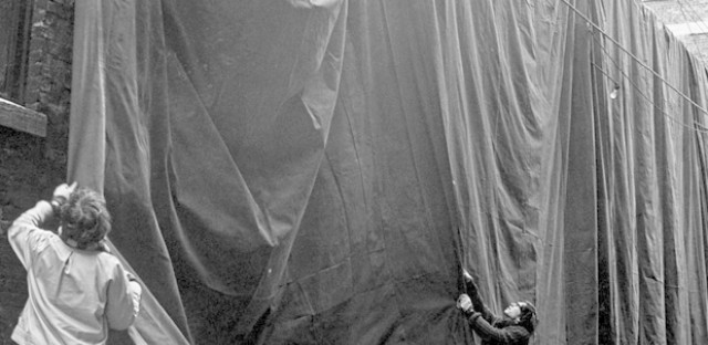Christo and an assistant adjust the draping of one of the heavy sheets of tarpaulin suspended from the roof of the MCA.
