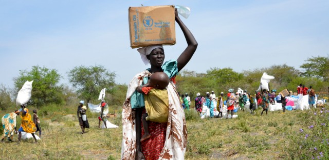 A woman carries food rations and her baby as she walks away from a World Food Program distribution in Jiech, Ayod County, South Sudan on Dec. 9, 2017. As South Sudan enters its fifth year of civil war, 1.25 million people are facing starvation, according to the latest analysis by the United Nations and the government. (AP Photo/Sam Mednick)