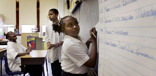 Then-sixth-grader Amber Willingham copies her homework assignment from a list on the board at the Kellogg Elementary School on June 6, 2005.