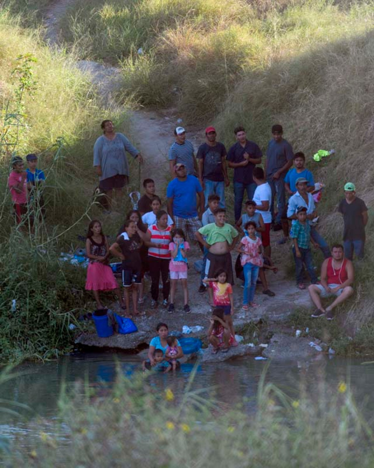 Migrants sit by the Rio Grande and look up to the bridge that connects Matamoros, Mexico and Brownsville, Texas. Paul Goyette