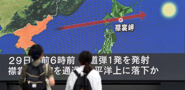 Passersby look at the North Korean missile's path over Japan, displayed on a huge screen in Tokyo on Wednesday. Japanese Prime Minister Shinzo Abe said he and President Trump have agreed to hike pressure on Kim Jong Un's regime after it launched a ballistic missile over the island of Hokkaido.