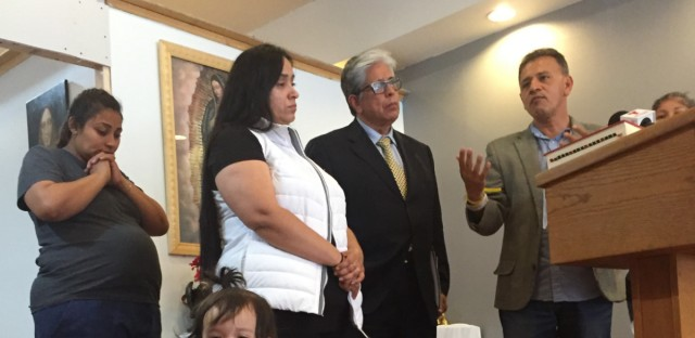 Nora Quiñones, wearing white vest, stands next to immigration attorney Juan Soliz and Pastor Jose Landaverde.