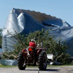Bernie Burla drives a tractor past a damaged grain silo on his family farm Tuesday, June 23, 2015, in Coal City, Ill., after a tornado passed through the Coal City area Monday evening. The National Weather Service confirmed a twister touched down in the community of approximately 5,000 residents, about 60 miles southwest of Chicago.