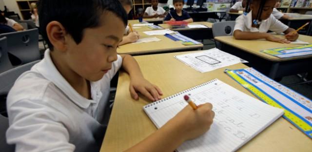 Jaeden Alvarez practices cursive writing at Cleveland K-6 School, Wednesday, Sept. 18, 2013, in Dayton, Ohio.