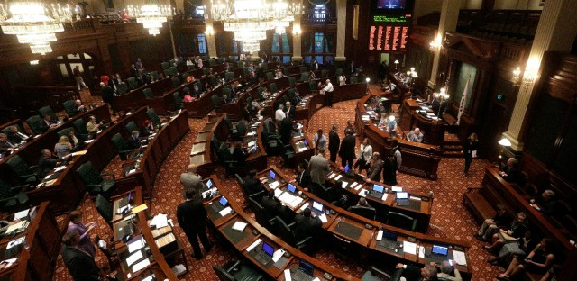 Illinois representatives gather on the House floor during session at the Illinois State Capitol in Springfield, Ill. on May 31, 2016.