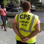 Safety guard Renee Green watches as parents walk with their children on the first day of school in Chicago.