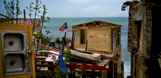 In this Oct. 5, 2017 photo, a Puerto Rican national flag is mounted on debris of a damaged home in the aftermath of Hurricane Maria in the seaside slum La Perla, San Juan, Puerto Rico. With tourism to Puerto Rico as a whole abruptly halted, the only visitors to La Perla since the Sept. 20 storm have been people like the U.S. National Park Service workers who came to distribute bottles of water.