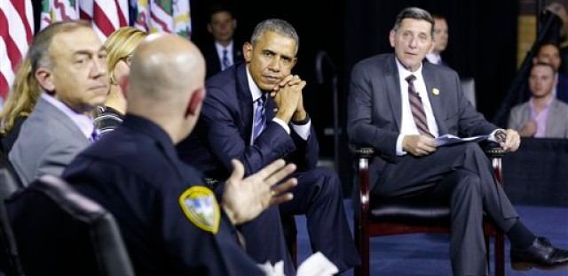 President Barack Obama, listens to Charleston Police Chief, Brent Webster, front as Dr. Michael Brumage, left, Director of Drug Control Policy, Michael Boticelli, right, listen during an event at the East End Family Resource Center in Charleston, W.Va., Wednesday, Oct. 21, 2015.