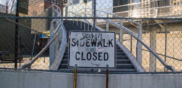 """""""Soon?!"""" asks a graffiti tag on a """"sidewalk closed"""" sign at a would-be entrance for the long-delayed Navy Pier Flyover. The project, which began in 2014, could take as long to complete as the construction of the Channel Tunnel that connects England to France."""