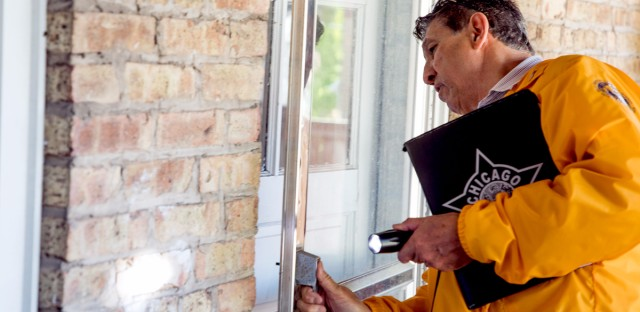 Richard Concaildi checks the back door of a vacant apartment unit in West Rogers Park to make sure it is securely locked. A neighbor had alerted him that it may be occupied by squatters.