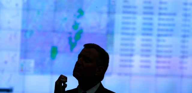 New York City Mayor Bill de Blasio watches a presentation about Shotspotter during a news conference at police headquarters in New York, Monday, March 16, 2015.