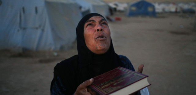 An Iraqi displaced woman who fled with her family from the Iraqi northern city of Mosul, prays after receiving a copy of the Quran from a Kurdish local charity organization at a camp in Khazer on Saturday, June 28, 2014.