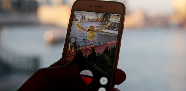 A fan plays the mobile game Pokemon Go.