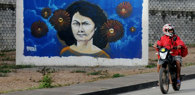 A motorcyclist rides past a mural of slain environmentalist and indigenous leader Berta Caceres in Tegucigalpa, Honduras in January 2017. The international watchdog group Global Witness says Honduras is the most dangerous country in the world for environmental defenders, with more than 120 of them killed there since 2010.  (AP Photo/Fernando Antonio)