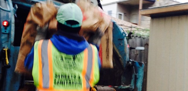 A city sanitation worker places yard waste in a truck with regular trash.