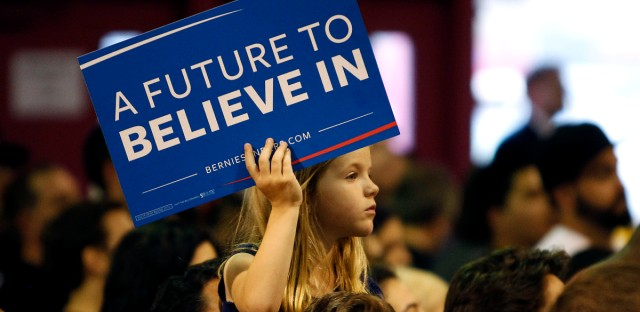 A young campaign supporter for Democratic presidential candidate Sen. Bernie Sanders, I-Vt., holds up a sign during a campaign rally, Saturday, March 19, 2016 in Phoenix.