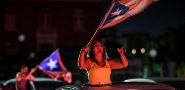 People celebrate, after Gov. Ricardo Rossello announced that he is resigning Aug. 2 after nearly two weeks of protests and political upheaval touched off by a leak of crude and insulting chat messages between him and his top advisers in San Juan, Puerto Rico, Thursday, July 25, 2019.