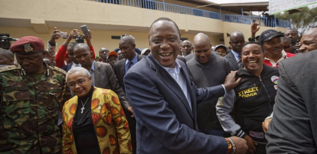 Kenyan President Uhuru Kenyatta (center) shakes hands with supporters after casting his vote in the city of Gatundu on Tuesday.