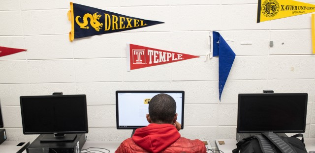 A student sits at a computer with college flags hanging on the wall  above