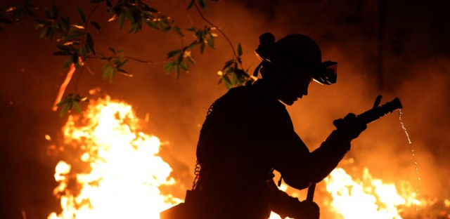 Cal Fire firefighter Trevor Smith battles the Tubbs Fire near Calistoga, Calif., on Thursday. Wildfires in Northern California have killed dozens of people and thousands of homes and businesses.