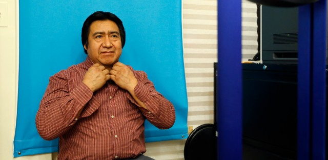 Luis Gordillo, a carpenter from Ecuador, adjusts his shirt collar as he has his picture taken while applying for a New York City municipal ID card at Make the Road New York in the Queens section of New York, Friday, Feb. 27, 2015. A municipal ID program that city officials thought would draw a few hundred thousand people in its first year has been much more popular than anticipated, with New Yorkers waiting hours in line and months for appointments to register. City officials have scrambled to keep up with the demand.