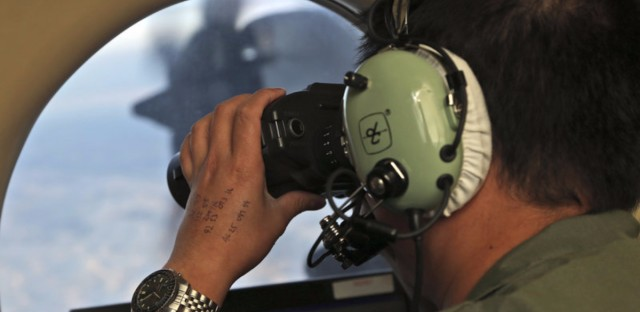 Flight Officer Jack Chen uses binoculars at an observers window on a Royal Australian Air Force P-3 Orion during the search for missing Malaysia Airlines Flight 370 in the southern Indian Ocean in March 2014. (Rob Griffith/AP)