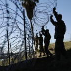 Members of the U.S. military install multiple tiers of concertina wire along the banks of the Rio Grande near the Juarez-Lincoln Bridge at the U.S.-Mexico border in Laredo, Texas in November. Eric Gay/AP