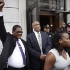 Bill Cosby looks on as his spokesman Andrew Wyatt triumphantly raises his fist outside the Montgomery County Courthouse in Norristown, Pa., on Saturday. Cosby's legal and publicity team treated the mistrial as a victory, though prosecutors immediately said they plan to retry the case.