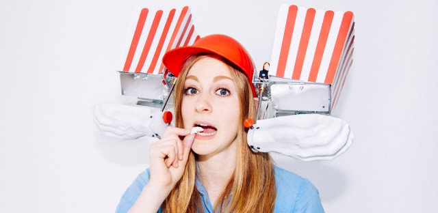 Simone Giertz wearing one of her inventions, The Popcorn Helmet