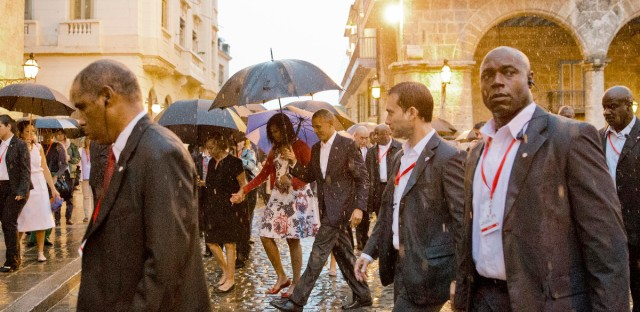 U.S. President Barack Obama, center, walks in the rain with first lady Michelle Obama, who is holding the arm of her mother Marian Robinson, during a walking tour of Old Havana, Cuba, Sunday, March 20, 2016. Obama became the first U.S. president to visit the island in nearly 90 years.
