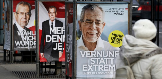 A woman passes posters of left-leaning presidential candidate Alexander van der Bellen in Vienna, Austria, Monday, Dec. 5, 2016. Van der Bellen defeated right-wing rival Norbert Hofer in Sunday's election, a victory welcomed by moderate politicians across Europe seeking to thwart advances by right-wing populist forces looking to weaken the European Union.