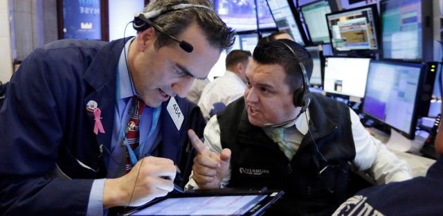 Traders Gregory Rowe, left, and Robert Finnerty work in their both on the floor of the New York Stock Exchange, Wednesday, Nov. 9, 2016. Stocks are moving solidly higher in midday trading on Wall Street following Donald Trump's upset victory over Hillary Clinton in the U.S. presidential election.
