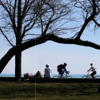 Aga Furtak, left, originally from Poland, and her friend Elliot Weis, take in the view and sun along Lake Michigan as two cyclists pass by at Chicago' North Avenue beach Friday, March 24, 2017. Temperatures climbed into the 70's prompting many to traverse the lakefront. (AP Photo/Charles Rex Arbogast)