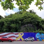 Afternoon traffic passes in front of a wall painted with the flags of the U.S. and Guam in the Tumon district on the island of Guam on Friday. The island has become a talking point in the rhetoric coming from President Trump and North Korea. Virgilio Valencia/AFP/Getty Images