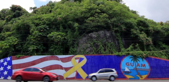 Afternoon traffic passes in front of a wall painted with the flags of the U.S. and Guam in the Tumon district on the island of Guam on Friday. The island has become a talking point in the rhetoric coming from President Trump and North Korea. (Virgilio Valencia/AFP/Getty Images)