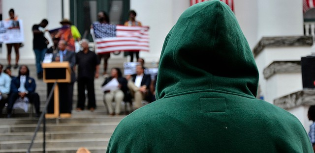 A man with hoodie watches the speakers on the steps of the Historic Capital Building in Tallahassee, Florida at a Rally March for Trayvon Martin