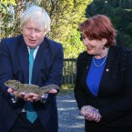 Britain's Foreign Secretary Boris Johnson holds a Tuatara lizard at Zealandia nature reserve as New Zealand Conservation Minister Maggie Barry watches in Wellington, New Zealand, Tuesday, July 25, 2017. Johnson is visiting the South Pacific nation for two days as Britain looks to strengthen its ties with its former colony amid a broader reshaping of Britain's global relationships as it prepares to leave the European Union. (Hagen Hopkins/Pool Photo via AP)