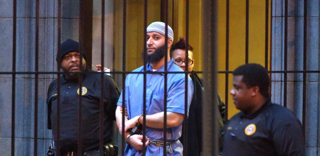 Officials escort Serial podcast subject Adnan Syed from the courthouse on Feb. 3 following the first day of hearings for a retrial in Baltimore. A judge granted the new trial — but on Thursday he denied Syed's motion to be released from jail while he waits for the retrial.