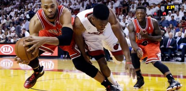 Chicago Bulls forward Taj Gibson, left, and Miami Heat guard Norris Cole battle for a loose ball as guard Nate Robinson, far right, watches during the first half of Game 2 of their NBA basketball playoff series.