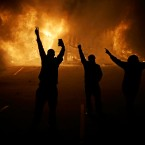 In this Nov. 25, 2014, file photo, people watch as stores burn in Ferguson, Mo., after the fatal police shooting of Michael Brown, a black 18-year-old who was unarmed. A federal judge has chosen a monitor team to oversee reforms of Ferguson's policing and court system. U.S. District Judge Catherine Perry announced Monday, July 25, 2016, that Squire Patton Boggs, a law firm based in Cleveland, was picked to make sure reforms are adequate in the St. Louis suburb.