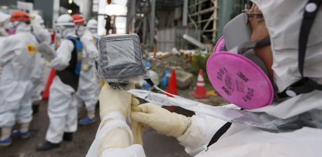 A Tokyo Electric Power Co. staffer measures the radiation level as others work on the construction of an ice wall at the Fukushima Dai-ichi plant on July 9, 2014. Kimmimasa Mayama/AFP/Getty Images