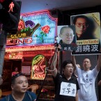 Pro-democracy activists hold photos of detained activists and those kept under surveillance including Liu Xia, left, and her husband and Nobel Peace Prize Laureate Liu Xiaobo, center, and Ding Zilin, founder of Tiananmen Mothers, during a protest in Hong Kong, Friday, June 30, 2017. Chinese President Xi Jinping landed in Hong Kong Thursday to mark the 20th anniversary of Beijing taking control of the former British colony, accompanied by a formidable layer of security as authorities showed little patience for pro-democracy protests. (AP Photo/Ng Han Guan)