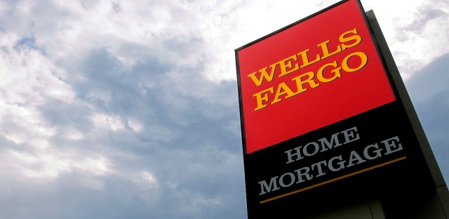 In this photograph taken July 19, 2010, the Wells Fargo logo is displayed on a sign outside one of the company's office buildings in Springfield, Ill. Wells Fargo & Co. said Wednesday, July 21, its second-quarter profit rose 21 percent as the growth of souring loans eased and it wrote off fewer defaults.