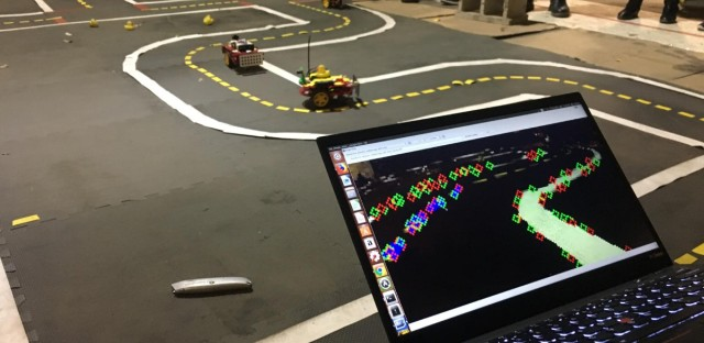 Students at the University of Illinois at Chicago watch small autonomous robot cars make their way around a road maze while also watching how the self-driving cars recognize their surroundings on a laptop. It's a class project that's part of a pilot class on self-driving cars introduced this semester.