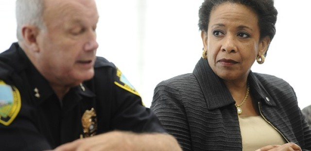 Attorney General Loretta Lynch listens as East Haven Police Chief Brent Larrabee speaks during a community policing tour, Tuesday, July 21, 2015, in East Haven, Conn. Lynch was in Connecticut to highlight improvements in relations between police and Latinos since four officers were arrested in 2012 on abuse charges.