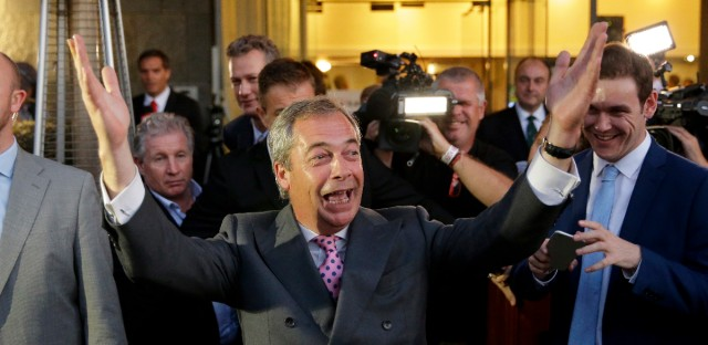 """Nigel Farage, the leader of the UK Independence Party, celebrates and poses for photographers as he leaves a """"Leave.EU"""" organization party for the British European Union membership referendum in London."""